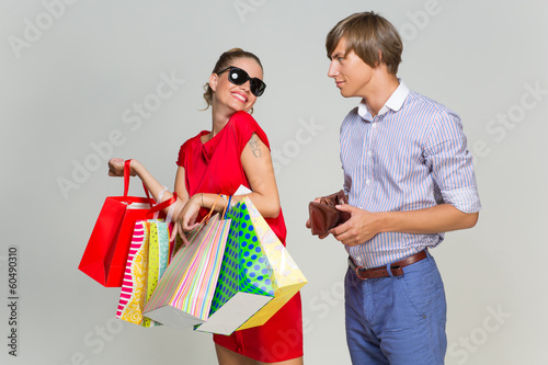 Young couple with many bags and empty wallet