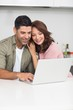 Happy couple using laptop in kitchen