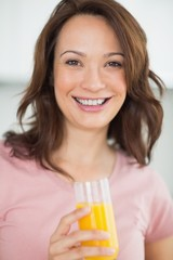 Portrait of a smiling woman holding orange juice