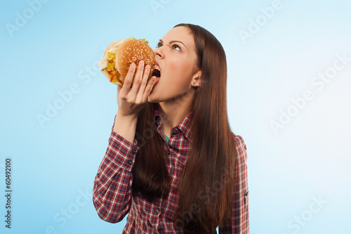 Girl eats a hamburger. Portrait in the studio.