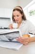 Woman with coffee cup reading newspaper in kitchen