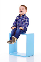 petit garçon assis sur un cube bleu