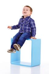 petit garçon assis sur un cube bleu bleu