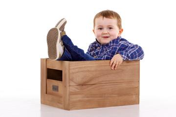 enfant assis dans une caisse en bois