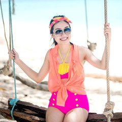 A portrait of beautiful asian sit on swing at the sea