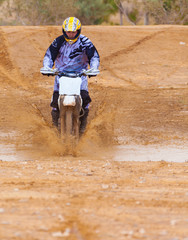 racer rides a motorbike through the mud