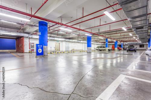 Leinwanddruck Bild Parking garage, underground interior with a few parked cars
