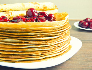 pancakes on a white plate and cherry