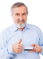 Senior man holding up a cash card