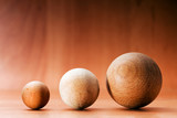 Three wooden balls on a wooden board.
