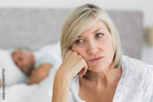 Tensed mature woman sitting in bed with man in background