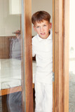 Surprised boy peeks from behind door