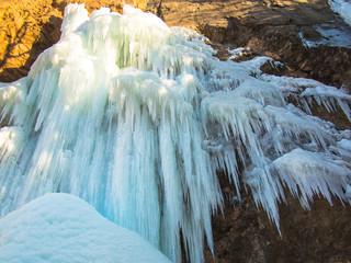 Frozen waterfall on a rock in the sunshine