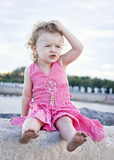 Little toddler sitting on the wharf