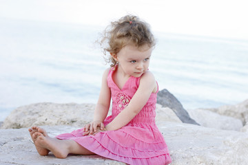 Little girl sitting on the shore and relaxing