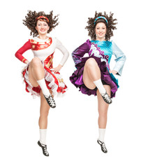 Two young women in irish dance dress dancing isolated