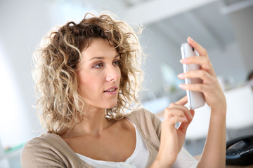 Woman in office sending message with smartphone
