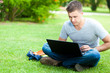 Student using laptop on the grass