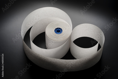Roll of cash register paper tape on black
