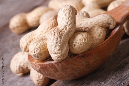 peanuts in shell closeup in brown wooden spoon