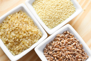 Wheat grains, bulgur and couscous on wooden background
