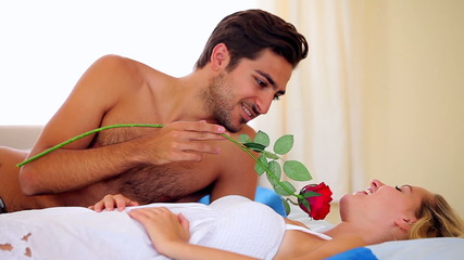 Man tickling his girlfriend with a rose on bed