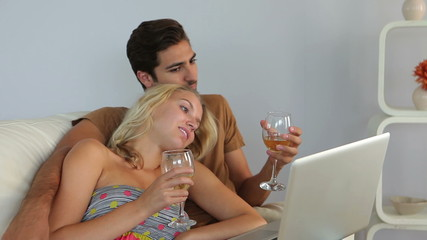Couple lying on couch watching laptop drinking wine