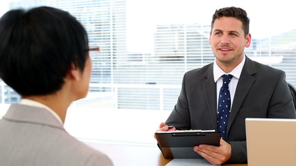 Handsome businessman talking with interviewee holding clipboard