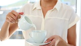 Pretty businesswoman pouring milk into cup