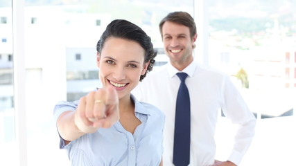 Businesswoman pointing at camera with colleague behind her