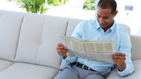 Businessman on couch reading newspaper