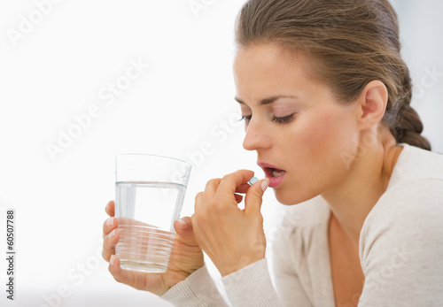 Young woman eating pills