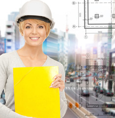 female contractor in helmet with folder