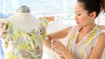 Fashion designer fixing dress on a mannequin