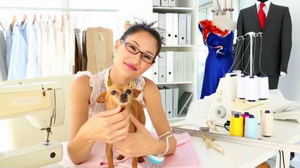 Pretty fashion designer petting her chihuahua