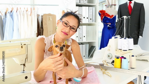 Pretty fashion designer petting her chihuahua