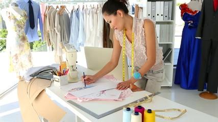 Fashion designer sketching a design at table