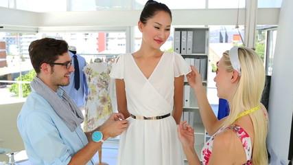Designers adjusting dress on model while chatting