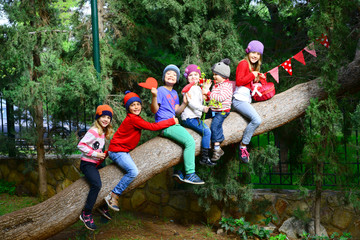 Group of happy kids sitting on a large tree trunk