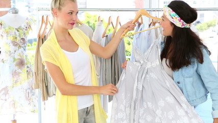 Friends admiring a dress and smiling at camera