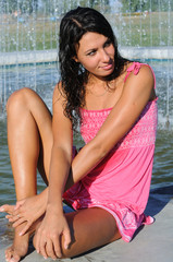 young attractive woman cooling near the fountain