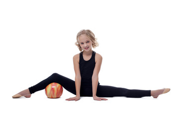 Cheerful flexible young gymnast posing on split