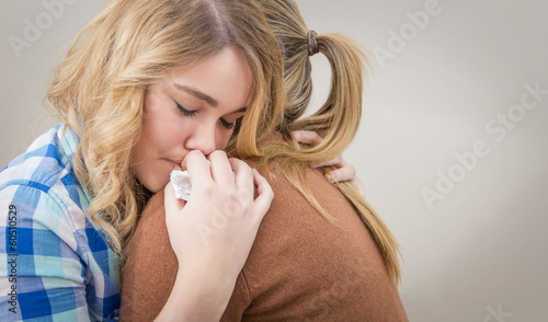 Fototapeta Mother embracing and soothes depressed daughter