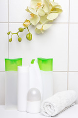 set of white cosmetic bottles with yellow orchid over tiled wall