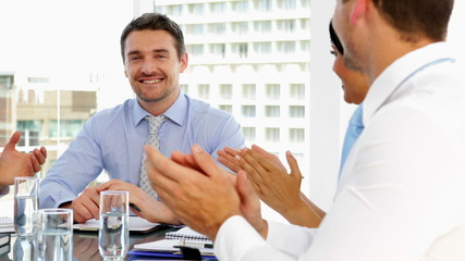 Business people applauding their boss during meeting