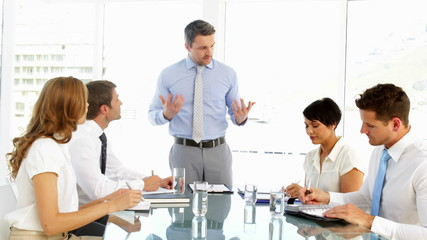 Businessman standing and speaking during meeting
