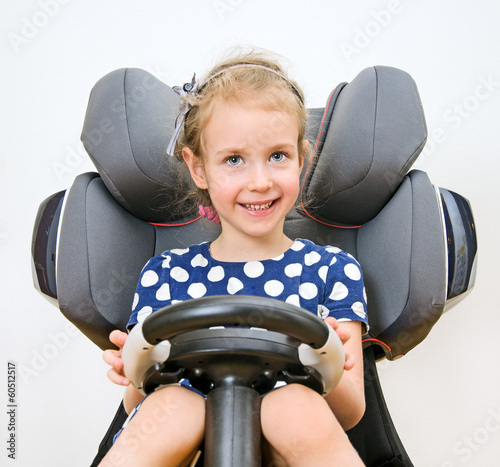 Little smiling girl holding steering wheel.