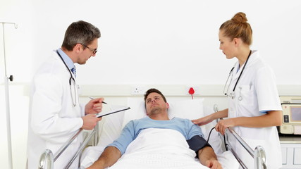 Doctor speaking with patient while nurse takes blood pressure