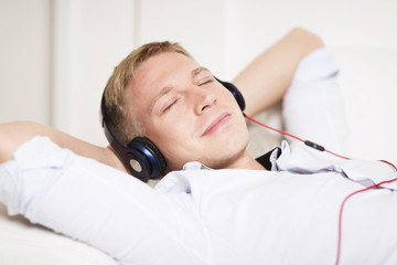 Smiling man enjoying listening music at headphones with eyes clo