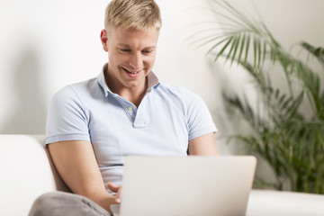 Cheerful young man sitting on couch with laptop.